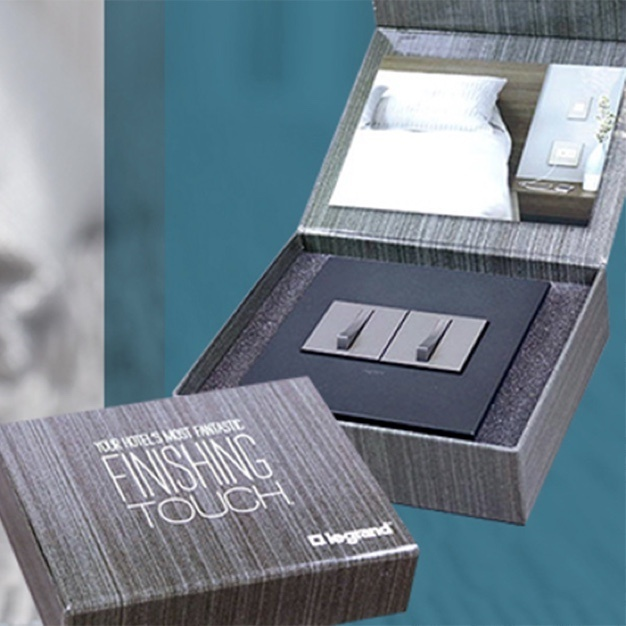 Gray sample box of adorne light switches on teal background