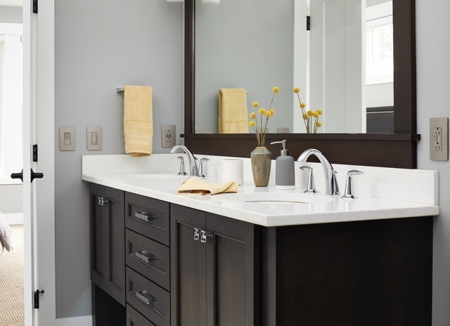 designer bathroom vanity with dark brown cabinets and white counter tops