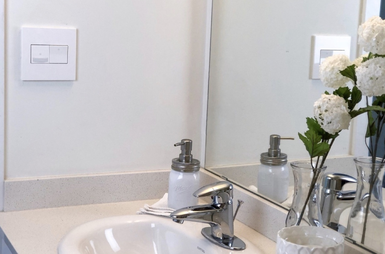 Legrand adorne Collection white motion sensor and paddle light switches on bathroom wall above sink
