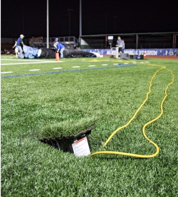 Outdoor ground box in grass with yellow cords emerging and student athletes in background