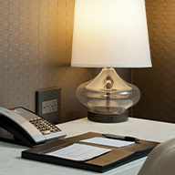Hotel desk with phone, lamp, and notepad