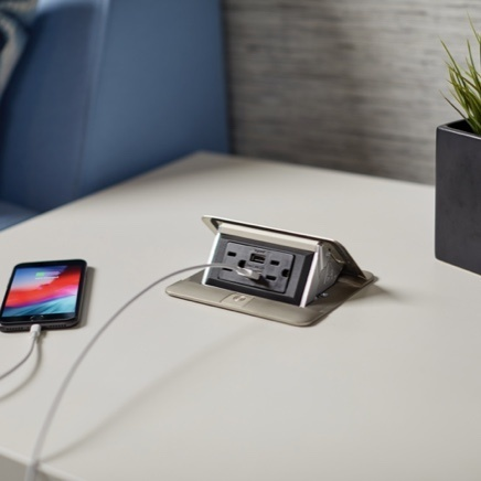 Flip-up power center on side table with phone charging in USB outlet