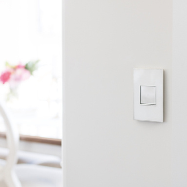 white switch on white wall with pink flower in the background
