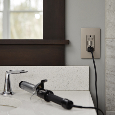 curling iron plugged into nickel gfci outlet on bathroom vanity