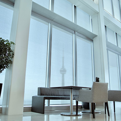 Small table, couch, and chairs in front of large windows in an office building