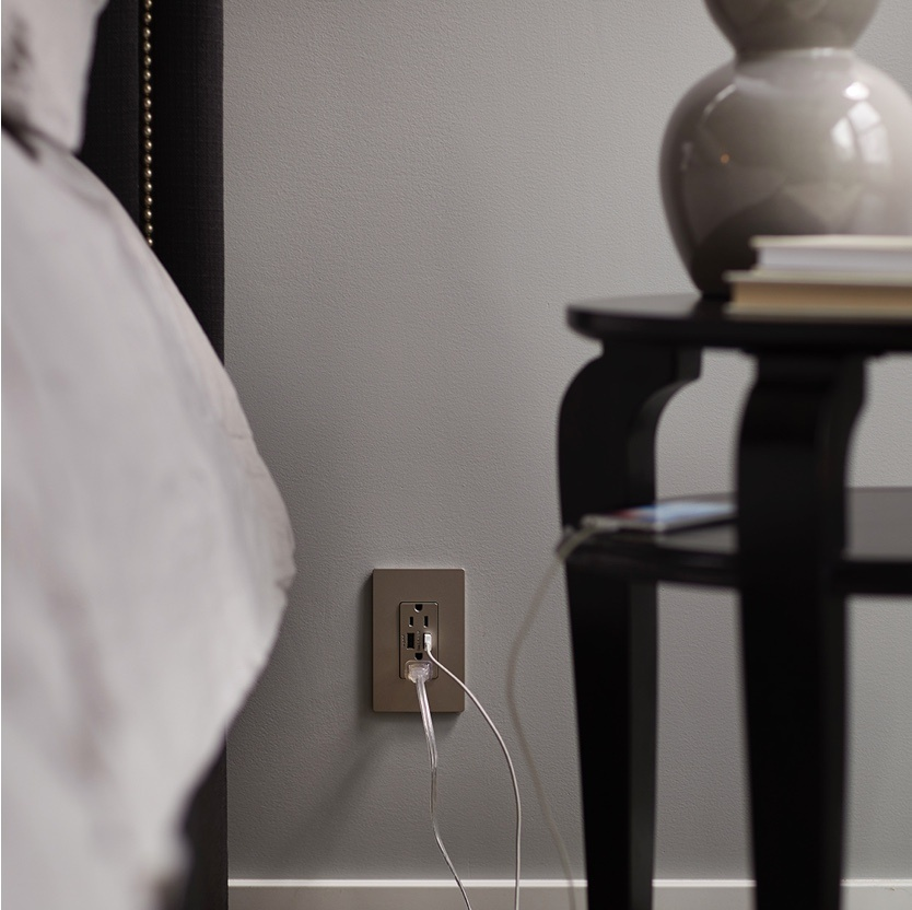 radiant Collection by Legrand metallic USB outlet with lamp and smart device plugged in next to bed