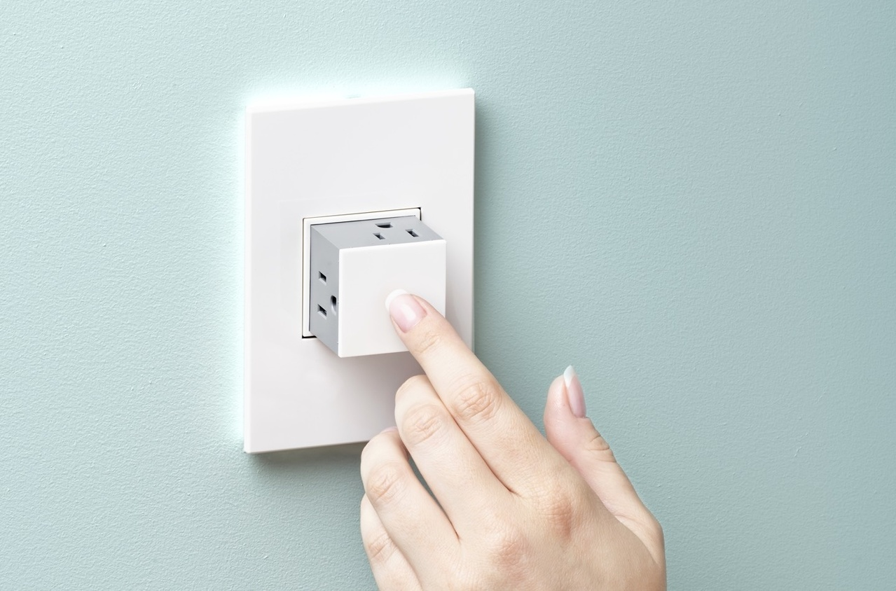Homeowner pressing the adorne Pop-out Outlet