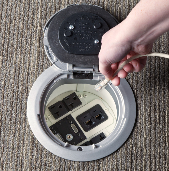 Open poke-thru device cover on carpet surface with hand reaching to plug in cable