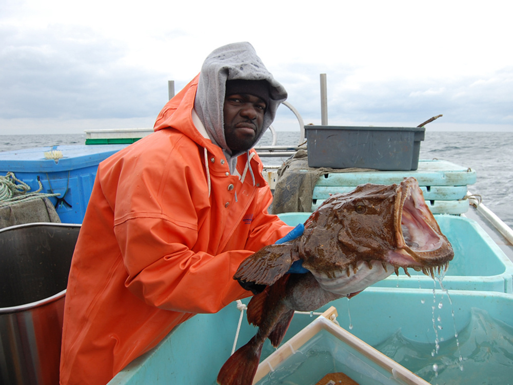 man holding tagged goosefish on boat