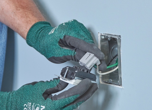 Contractor with gloved hands installing snap-in PlugTail outlet