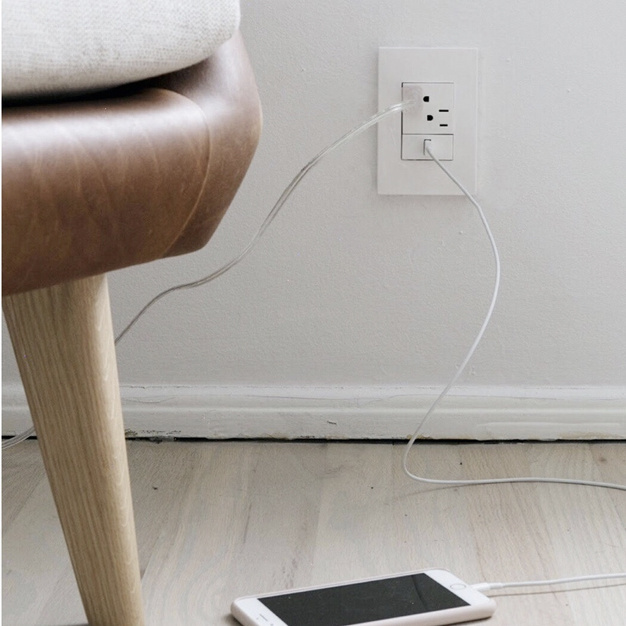 White usb outlet and wireless charger in white kitchen next to a bowl of lemons