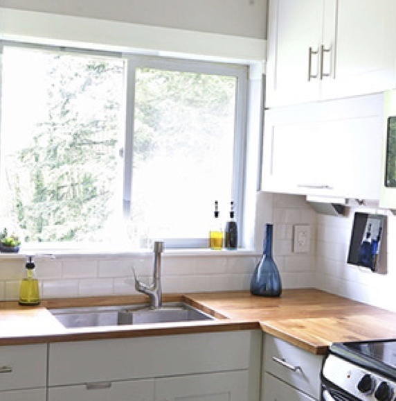 White kitchen with wooden counters and larger window