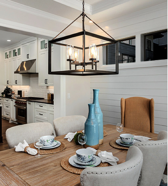 kitchen table with white shiplap walls and metal chandelier