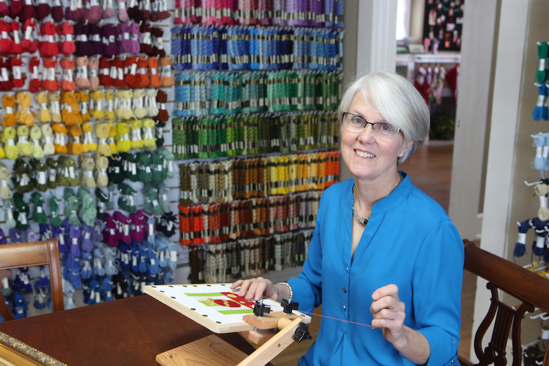 Judith Carter, owner of Needleworks, works on a holiday-themed needlepoint piece.