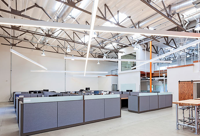 Commercial office space with high ceilings and large overhead lighting fixtures