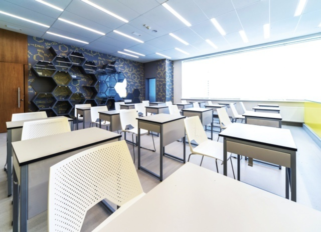 Brightly lit classroom with white chairs and school desks