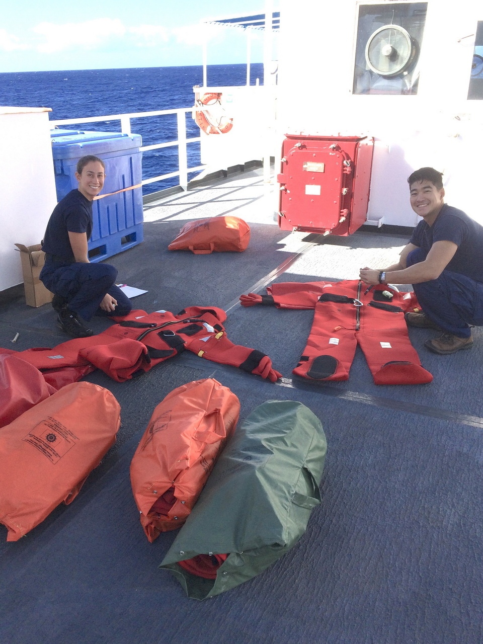 "Ensigns Moore and Park check the condition of survival suits (a.k.a. ""gumby suits"") before a weekly abandon ship drill. Photo: NOAA Fisheries/Suzanne Yin."