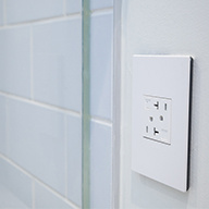 Side view of white outlet next to white tile