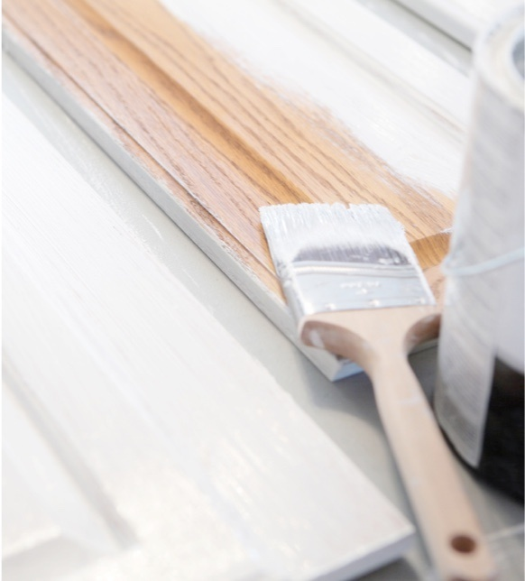 Paint brush with white paint lay on piece of wood