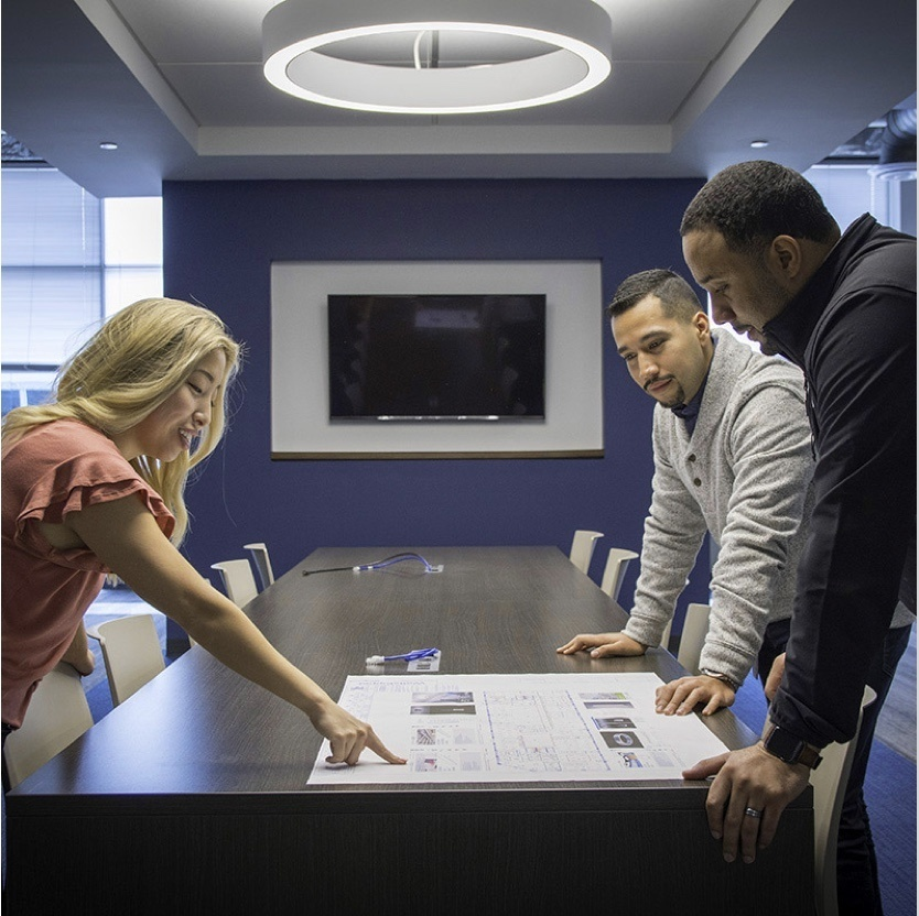 Two men and a woman standing around a conference table viewing QMotion product resources
