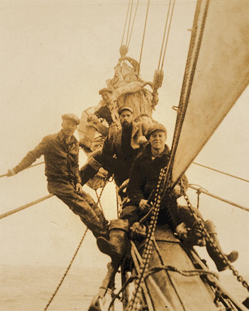 Men on the bowsprit of the schooner Wawona.