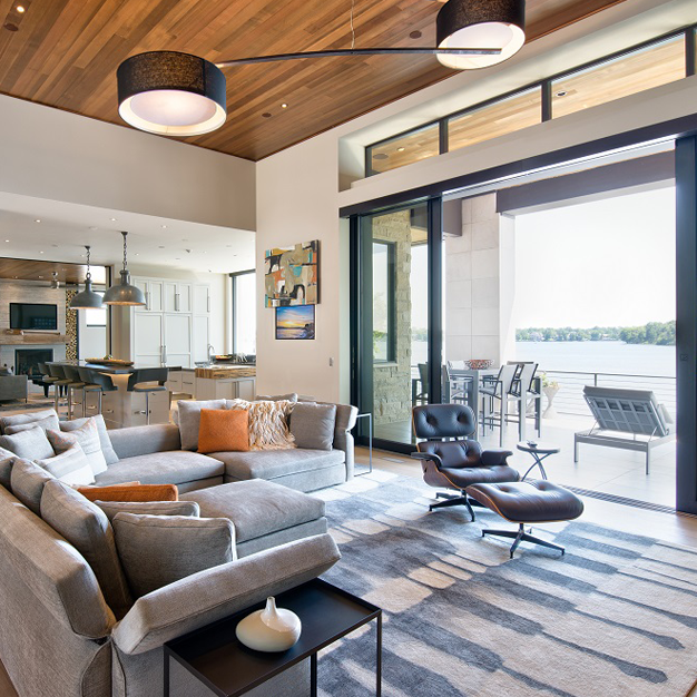Ceiling to floor sliding doors open to view a lake