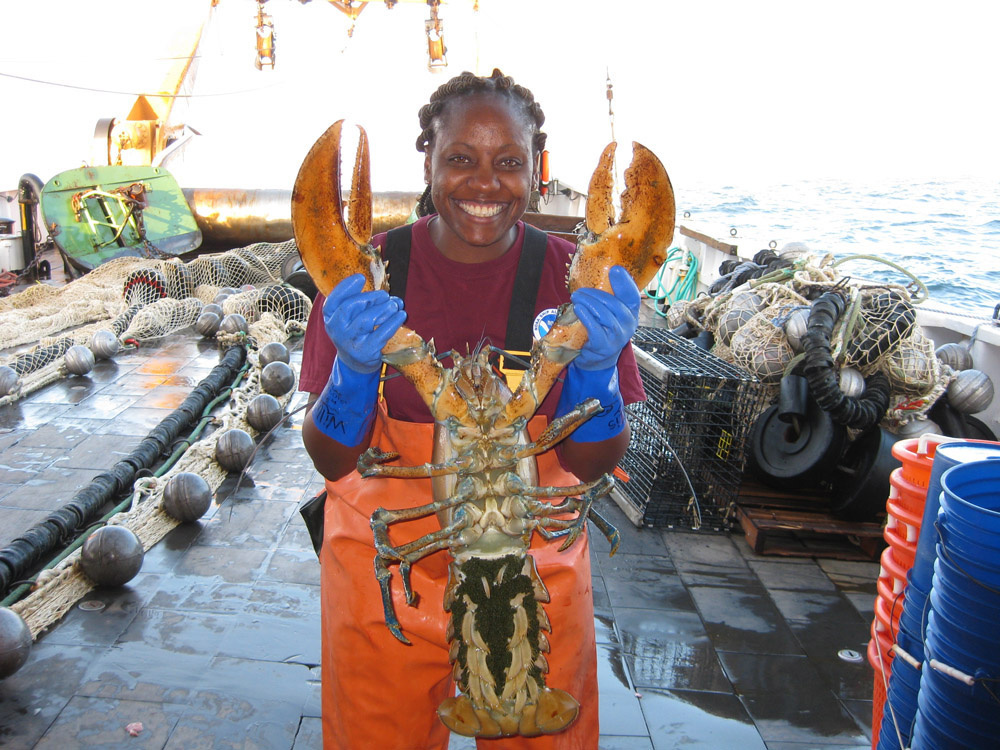 woman holding up large lobster with eggs
