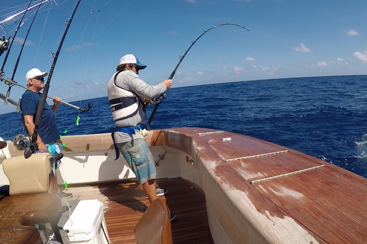 Recreational fishermen reeling in a fish on the line.