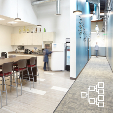 Open floor plan breakroom with someone reaching into the refrigerator, all next to a grey-carpetted hallway