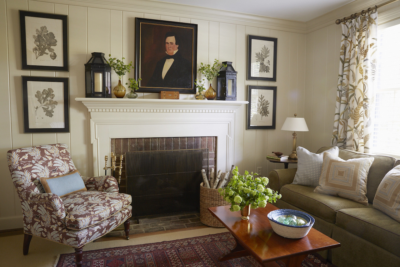 Family antiques fill the study, a favorite place for adults to retreat in the evening. Painting the bookcases, fireplace mantle and walls in a creamy beige warmed up the room without making it too dark and moody, adds Hennessy.  The color was chosen from the crewel curtains that the previous owners left behind.