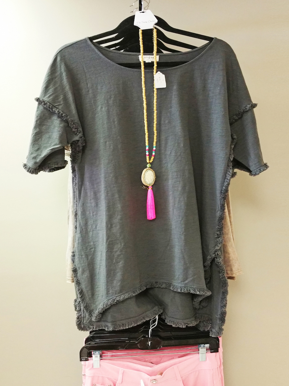 A casual tee is paired with a unique beaded, tassled necklace for a one-of-a-kind boho look!