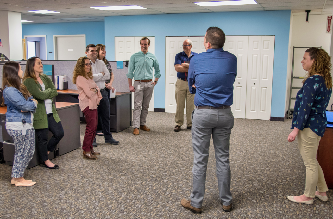 Legrand employees standing in a circle in the office