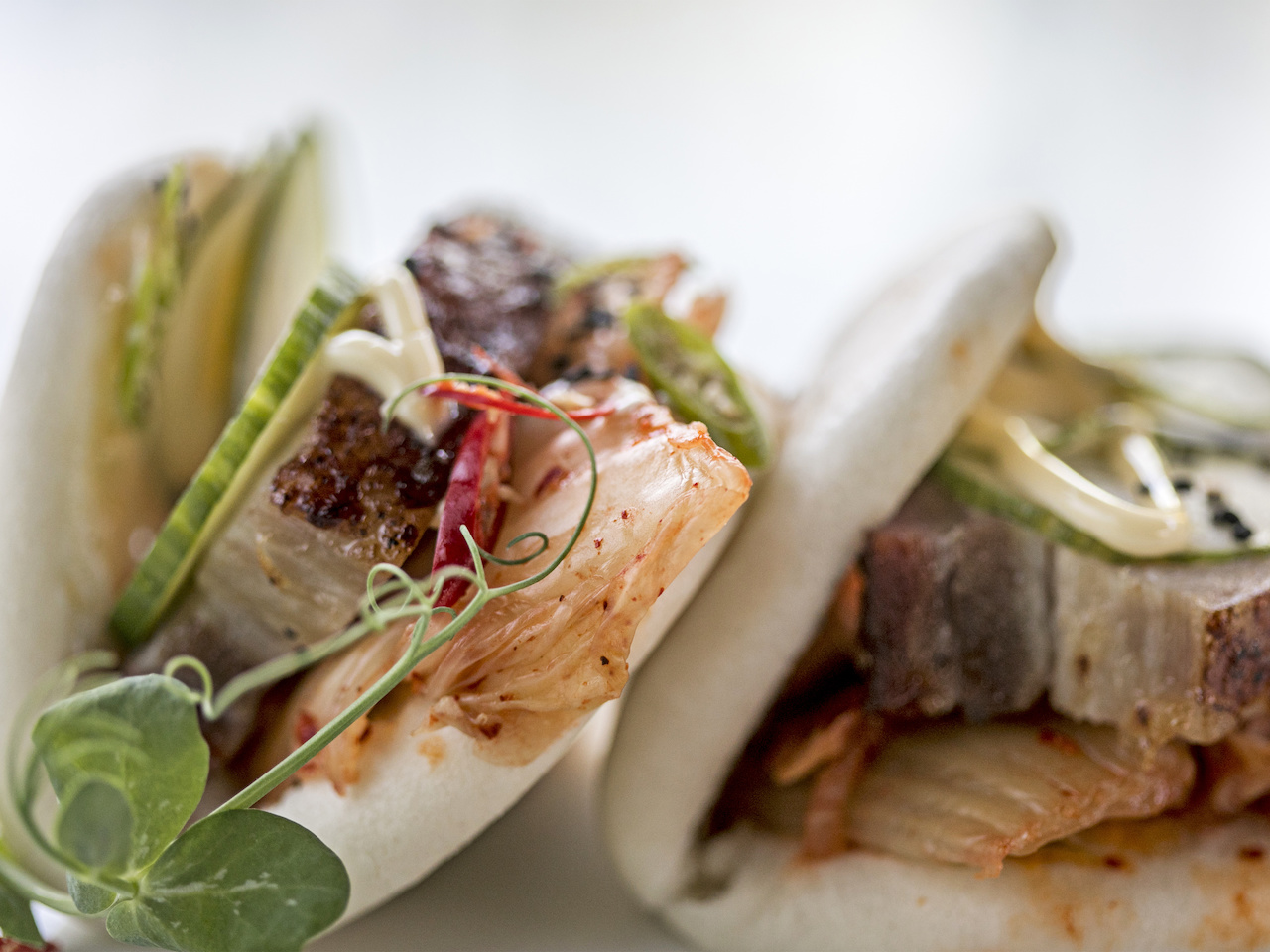 Pork belly buns feature house kimchi, spicy mayo and serrano peppers for $10.