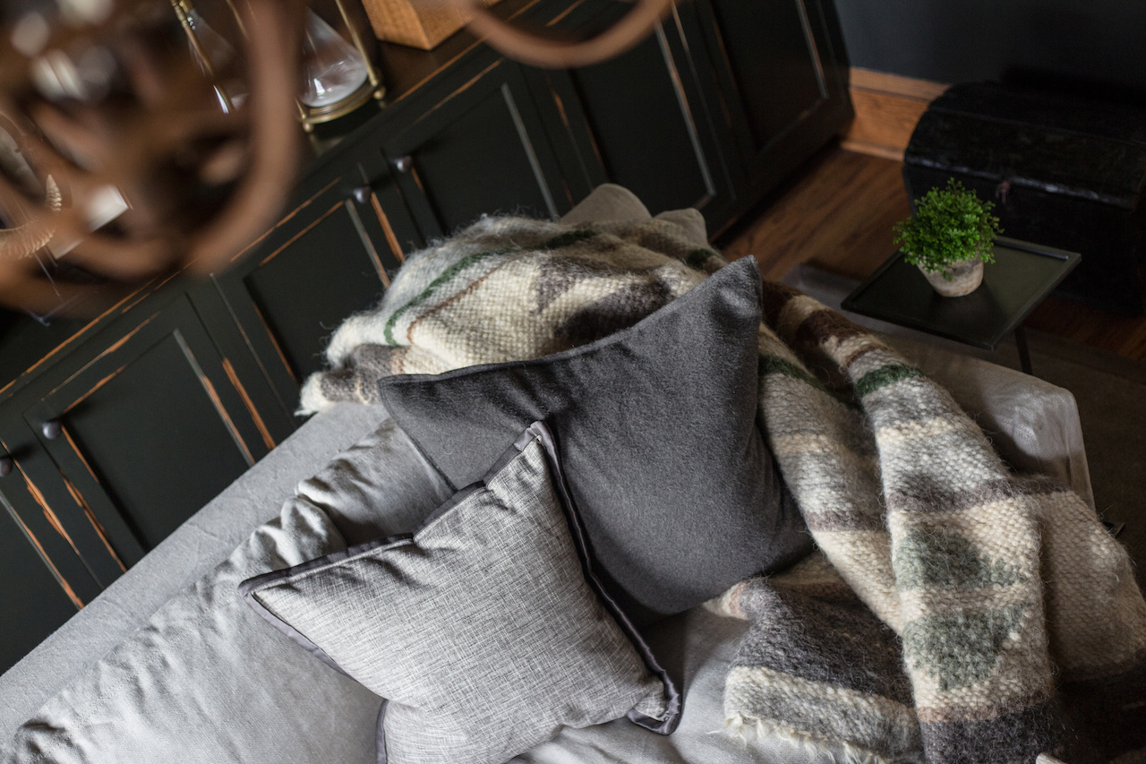 This dark and masculine space is softened with lighter colored fabrics, plush throws and pillows.