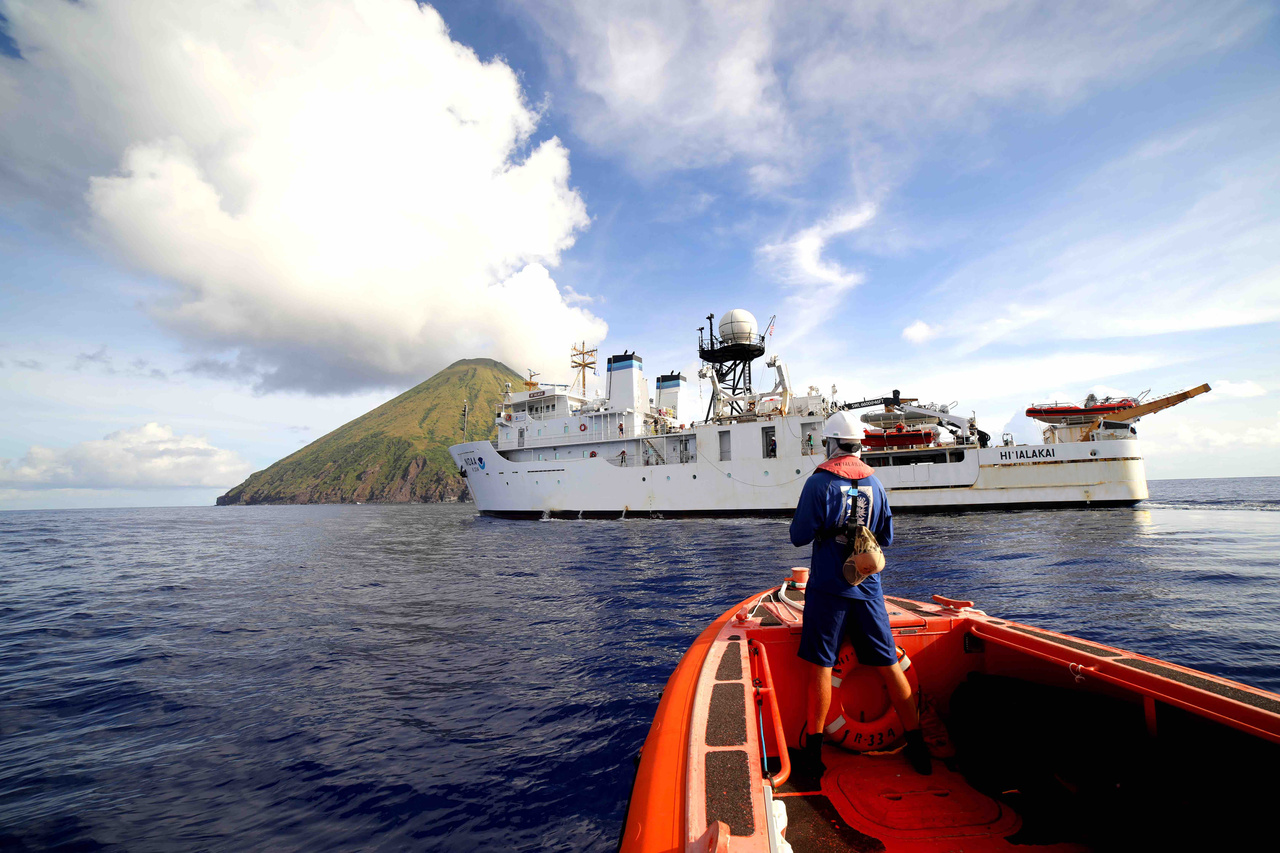Small boat approaches NOAA Ship Hi'ialakai at Asuncion Island in the Pacific Remote Islands.