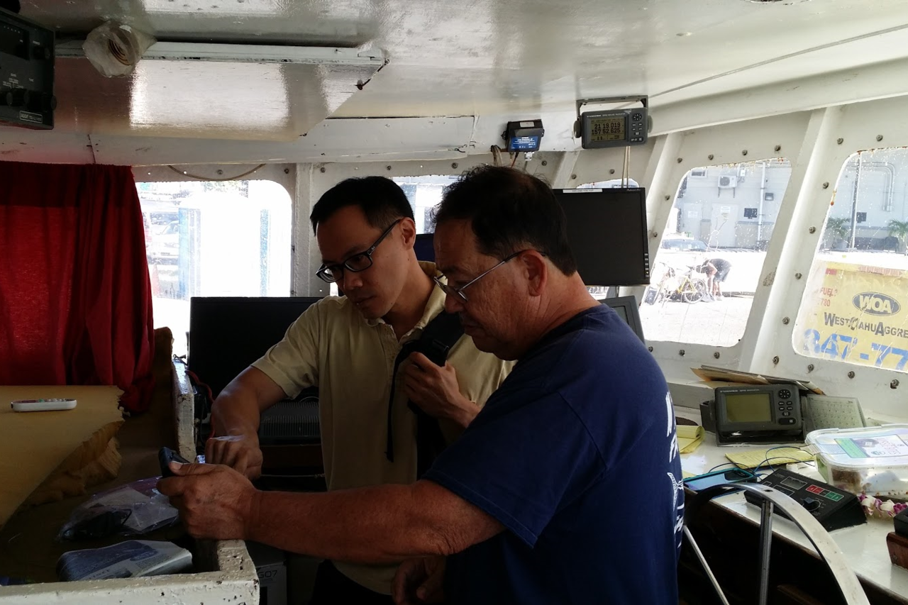 Nathan Chan, part of the Electronic Reporting team, works with a captain during setup and training.