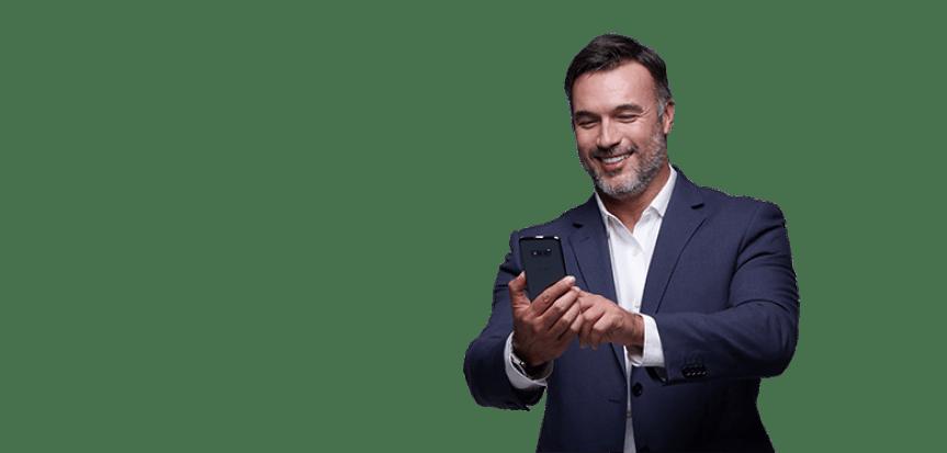Homem de terno sorri enquanto olha seu smartphone.