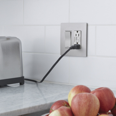 outlet and switch on kitchen counter with toaster plugged in