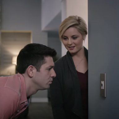 Man staring closely at light switch on wall and woman looking at him