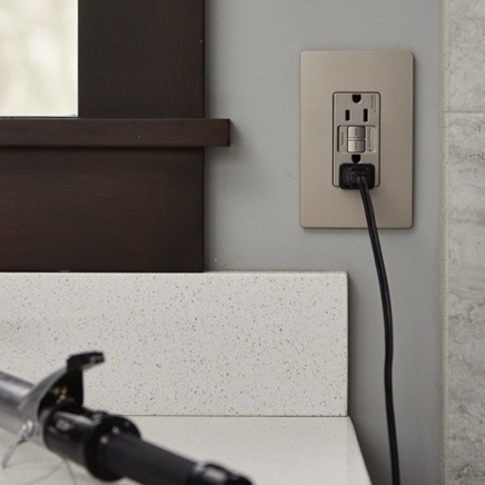 Designer GFCI installed in bathroom wall with curling iron charging
