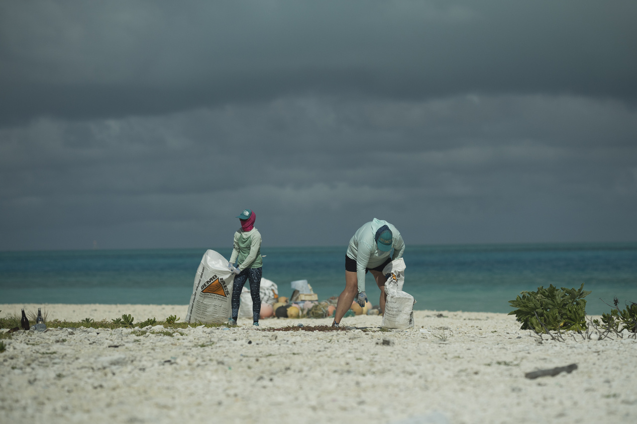 Miles and miles away from nearest major cities, plastics and fishing nets have accumulated along the shorelines of Midway Atoll. Scientists Williams and Weible collect debris on Eastern Island. [Lots of bending.] (Photo: NOAA Fisheries/Steven Gnam)