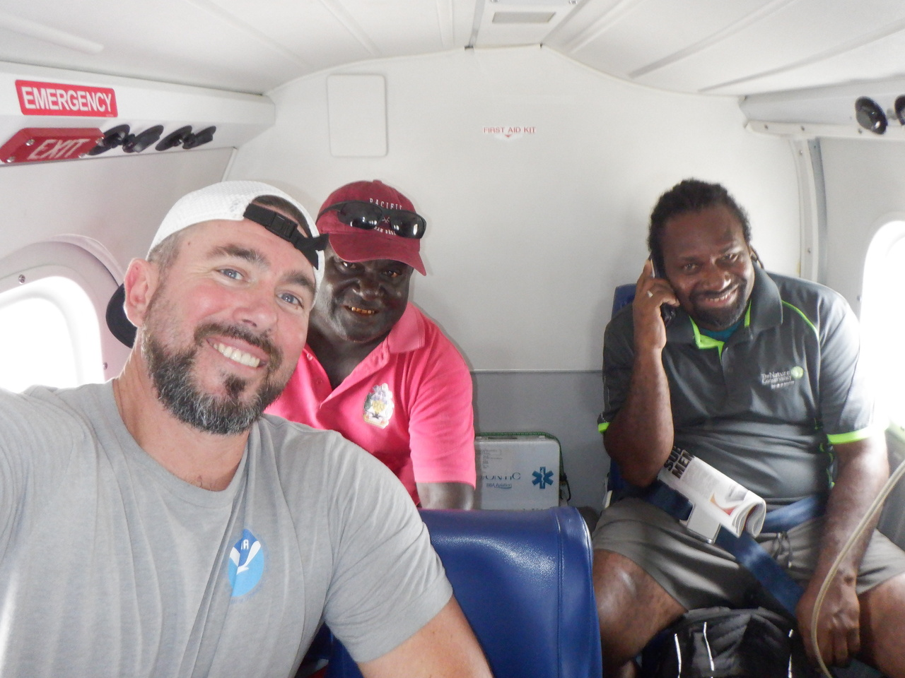 Three men in small plane smiling for camera.