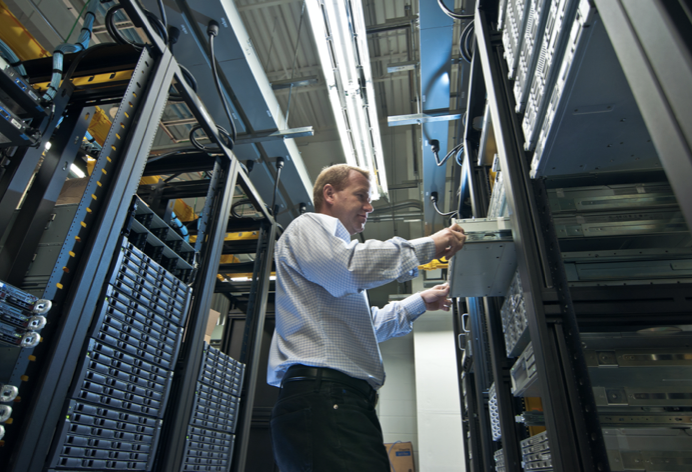 Data center technician working on a server inside a server cabinet