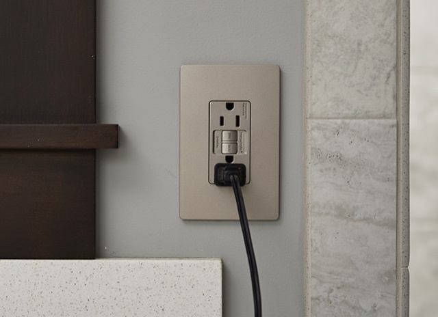 Legrand radiant Collection GFCI outlet in nickel on teal wall with black cord plugged in
