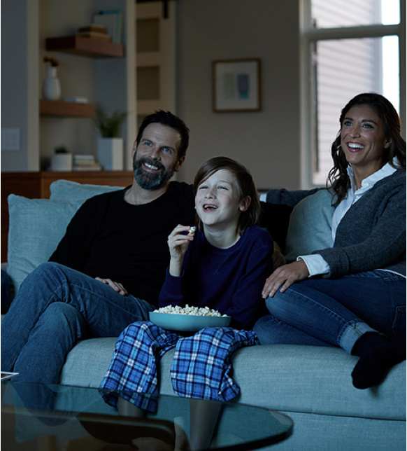 family of three sitting on blue couch eating popcorn in front of the television
