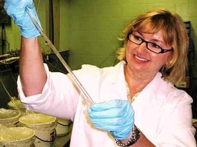 Women scientist holding beaker and pipette.