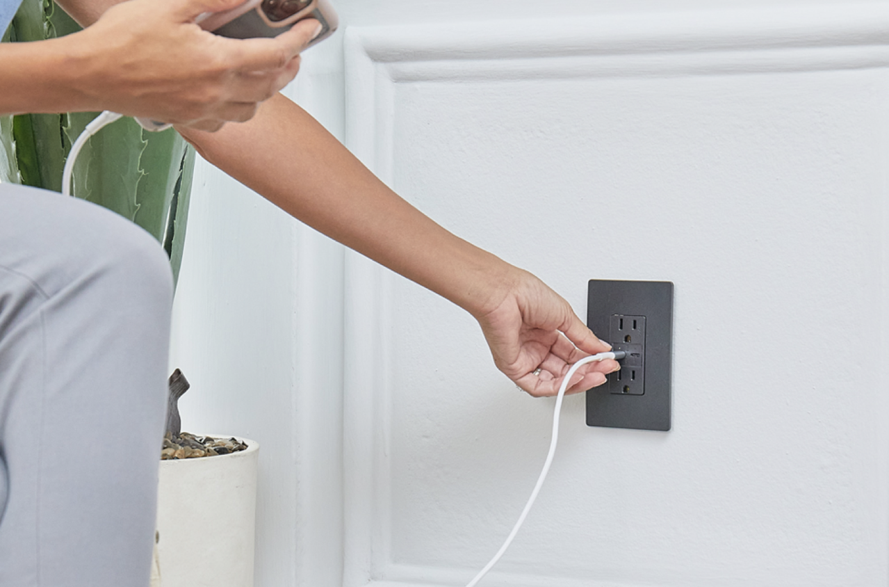 person plugging usb-c charger into adorne collection usb outlet