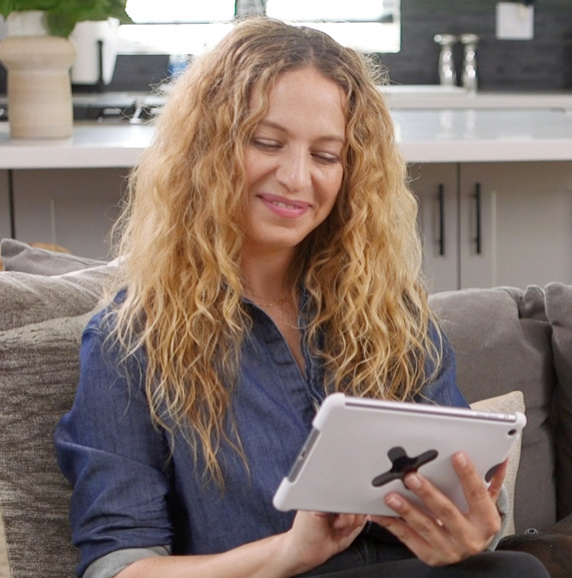 blonde woman in denim shirt holding white tablet while sitting on couch