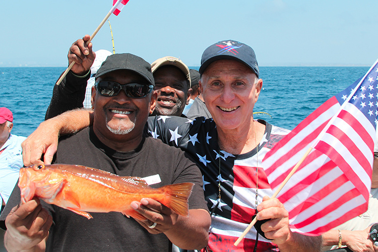 Three men on a rec fishing boat, holding American flags and a newly caught fish