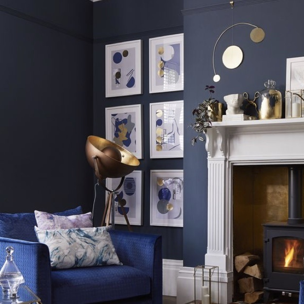 navy blue armchair with marbled pillows next to copper lighting fixture and gallery wall